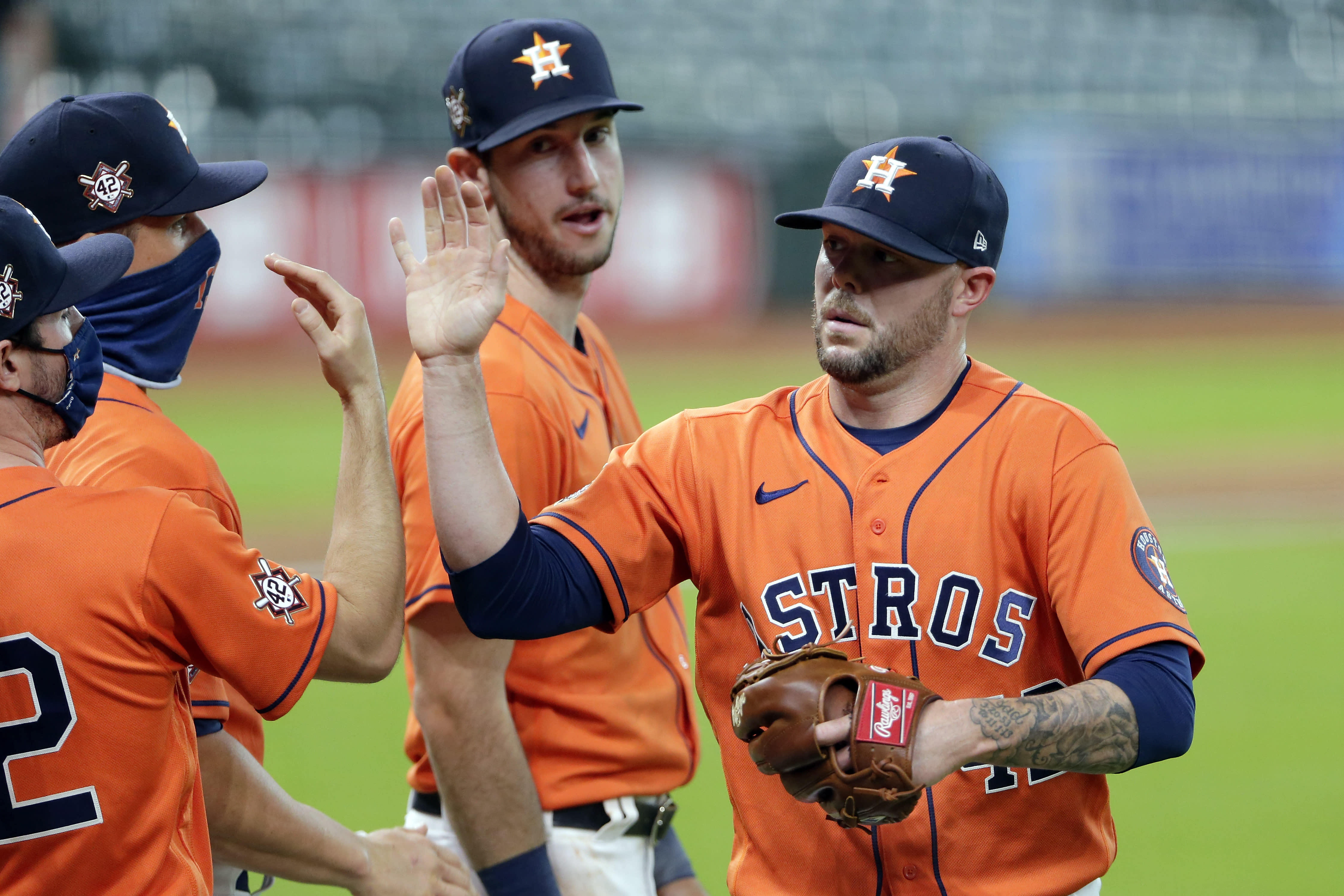 Houston Astros closing pitcher Ryan Pressly, right, collects near high-fives from teammates as Kyle Tucker, rear, watches after the team's 4-2 win over the Oakland Athletics in the first baseball game of a doubleheader Saturday, Aug. 29, 2020, in Houston. All players and managers are wearing No. 42 as a tribute to baseball great Jackie Robinson. (AP Photo/Michael Wyke)