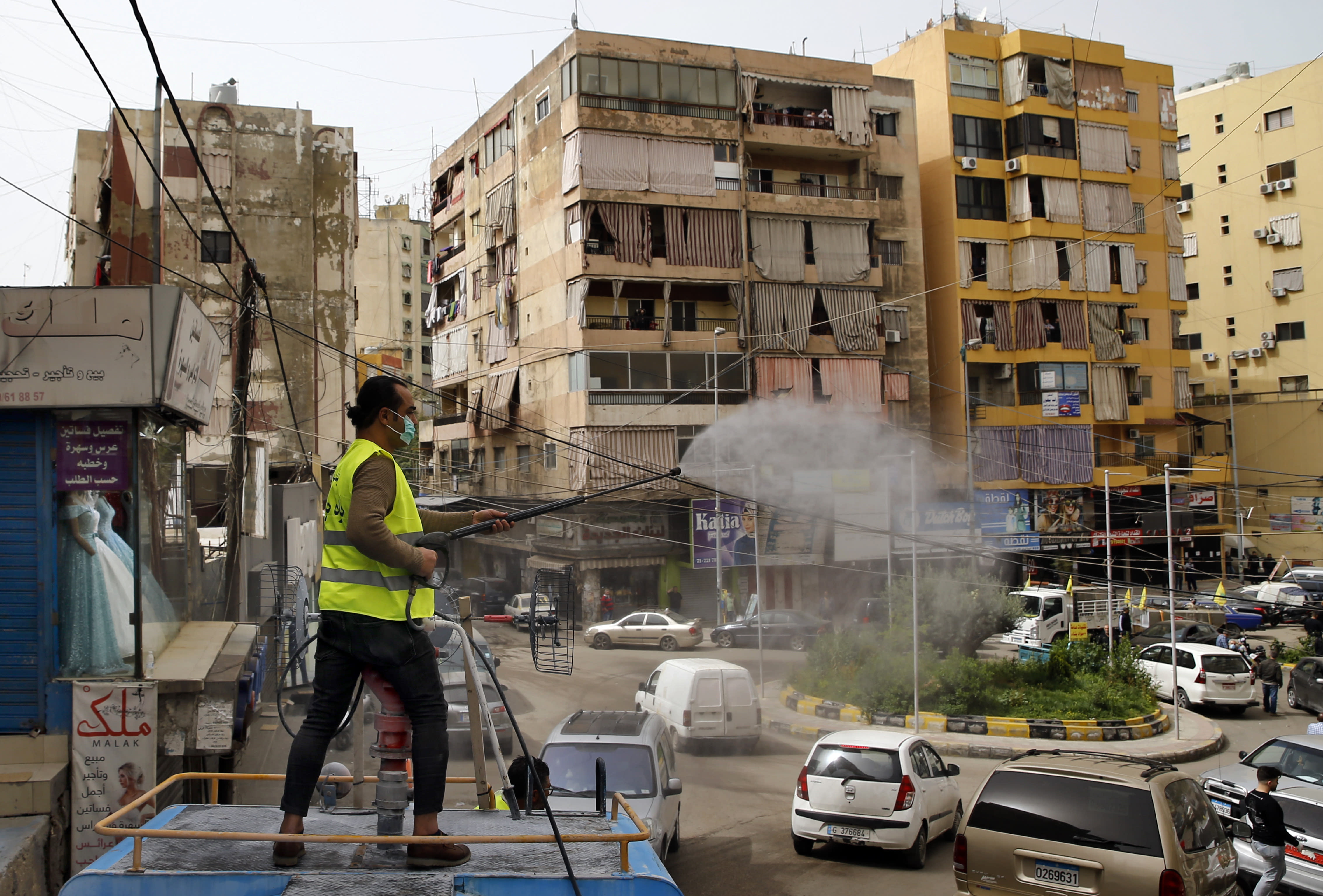 A municipal worker sprays disinfectant as a precaution against the coronavirus outbreak, in the southern suburb of Beirut, Lebanon, Friday, March 27, 2020. The virus causes mild or moderate symptoms for most people, but for some, especially older adults and people with existing health problems, it can cause more severe illness or death. (AP Photo/Bilal Hussein)