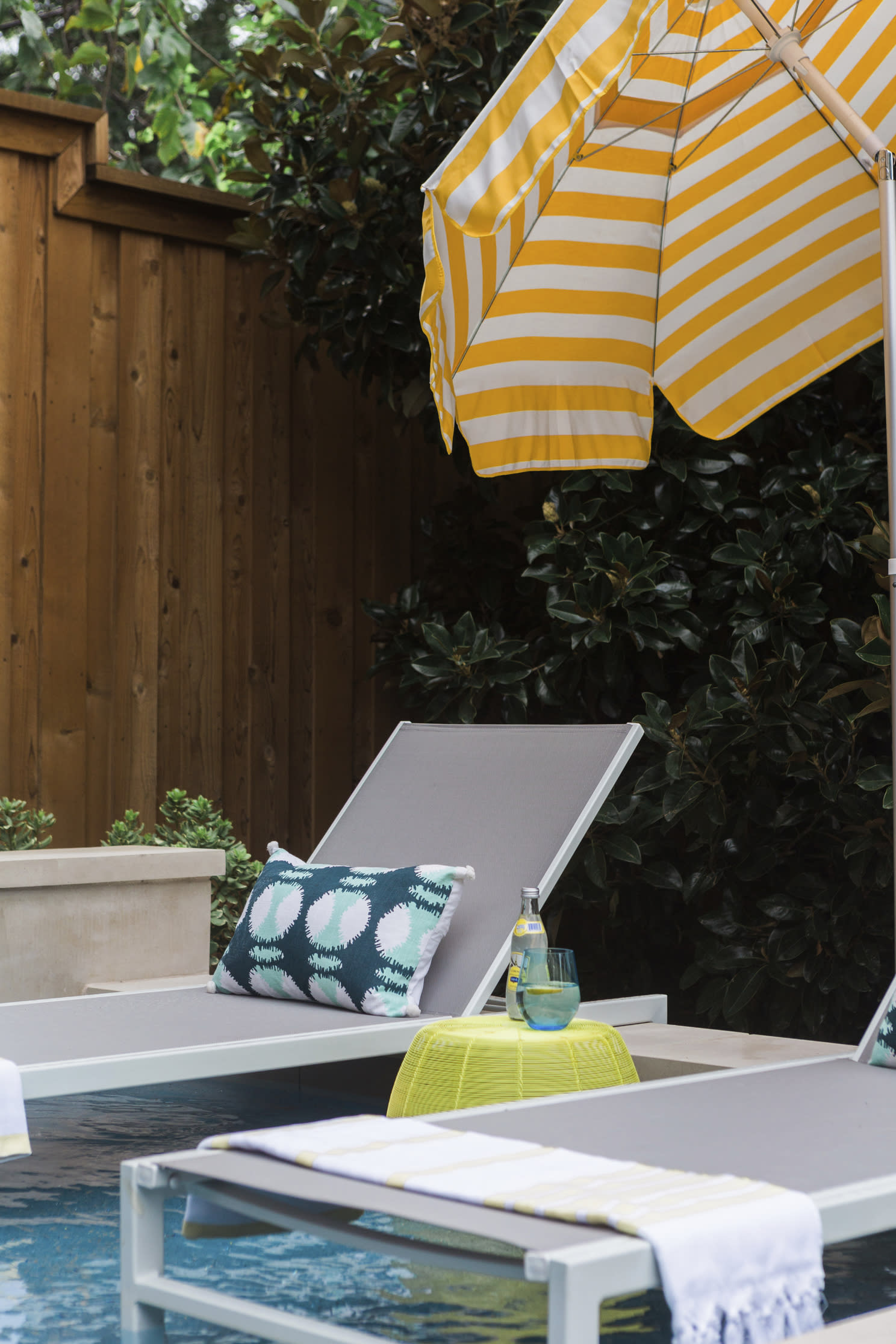 This undated photo shows a home in Texas' backyard area designed by Abbe Fenimore, founder of Studio Ten 25. The addition of stylish throw pillows and convenient cocktail tables next to poolside chaises can bring a bit of vacation resort experience to a backyard swimming pool. (Heather Hawkins/Abbe Fenimore via AP)
