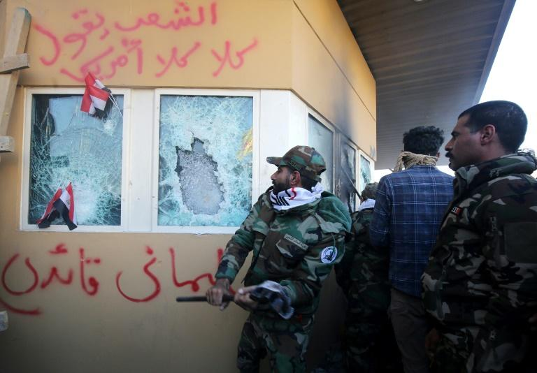 Members the Hashed al-Shaabi paramilitary network smash windows at the US embassy compound in Baghdad (AFP Photo/AHMAD AL-RUBAYE)