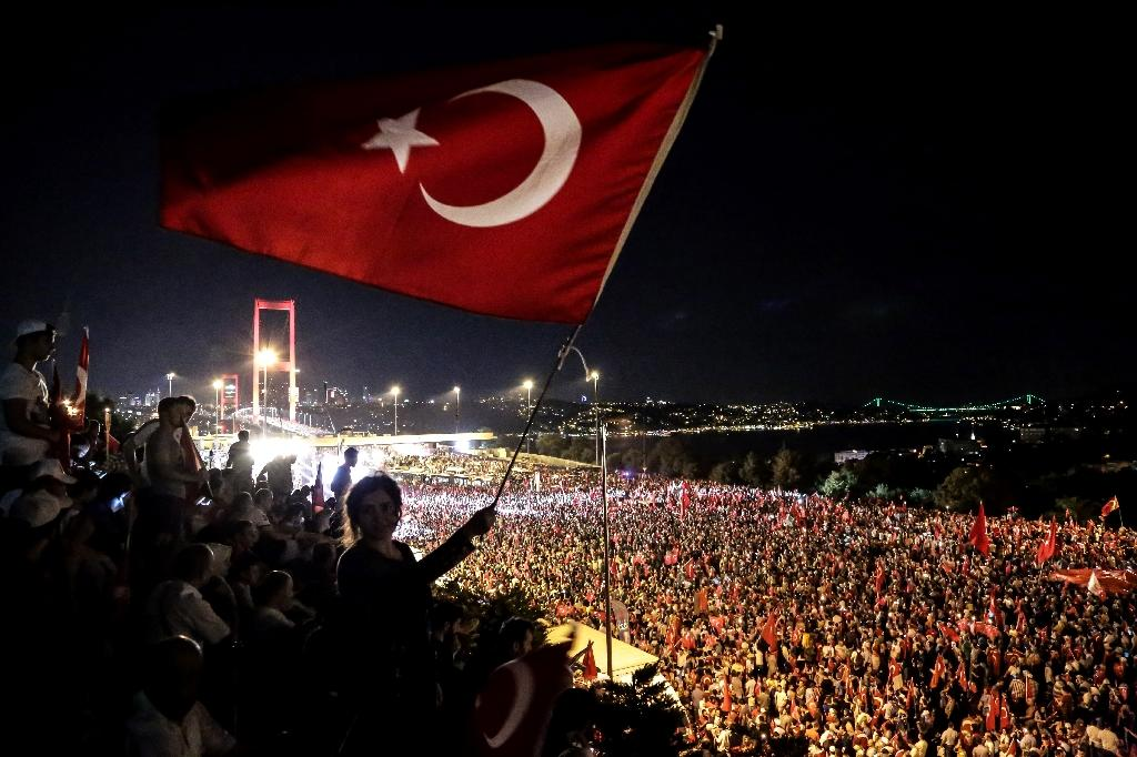 Pro-Erdogan supporters wave a Turkish national flag during a rally at the Bosphorus bridge in Istanbul on July 21, 2016