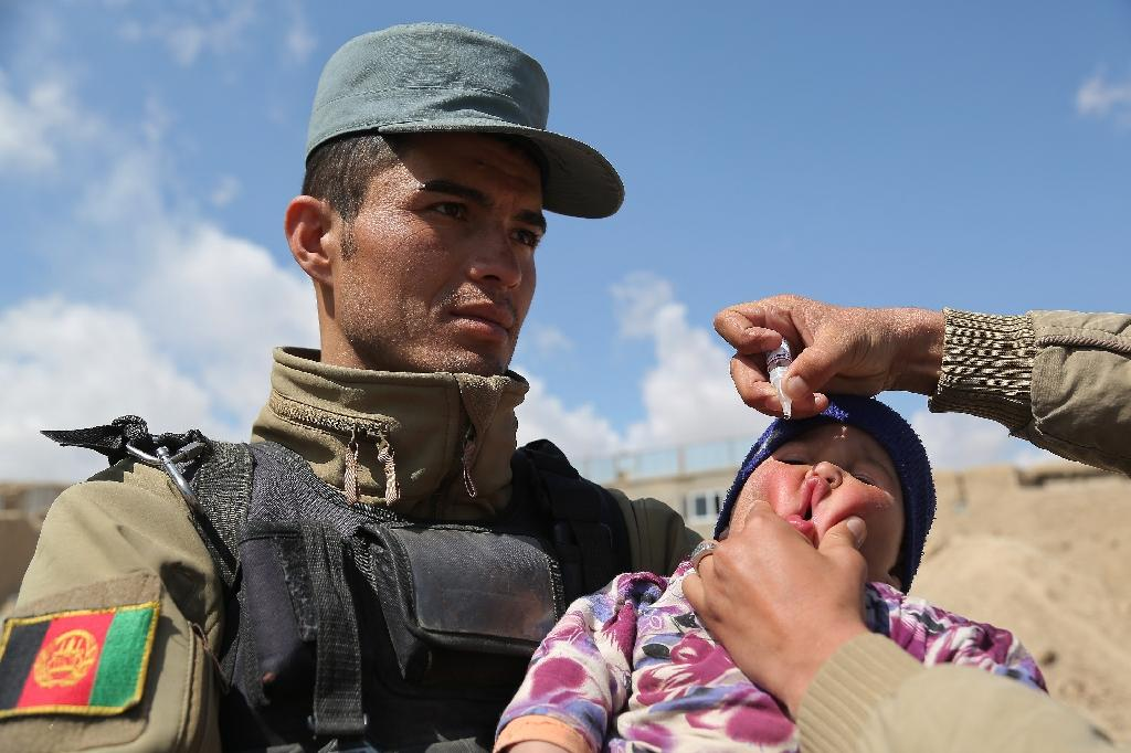 An Afghan policeman holds a child receiving the polio vaccine in Ghazni, in 2015 (AFP Photo/Rahmatullah Alizadah)