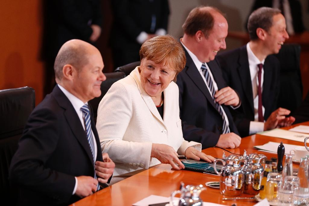 Joerg Kukies will step down as co-head of Goldman Sachs in Germany and Austria to become a state secretary under Angela Merkel's (2nd L) new finance chief Olaf Scholz (L)