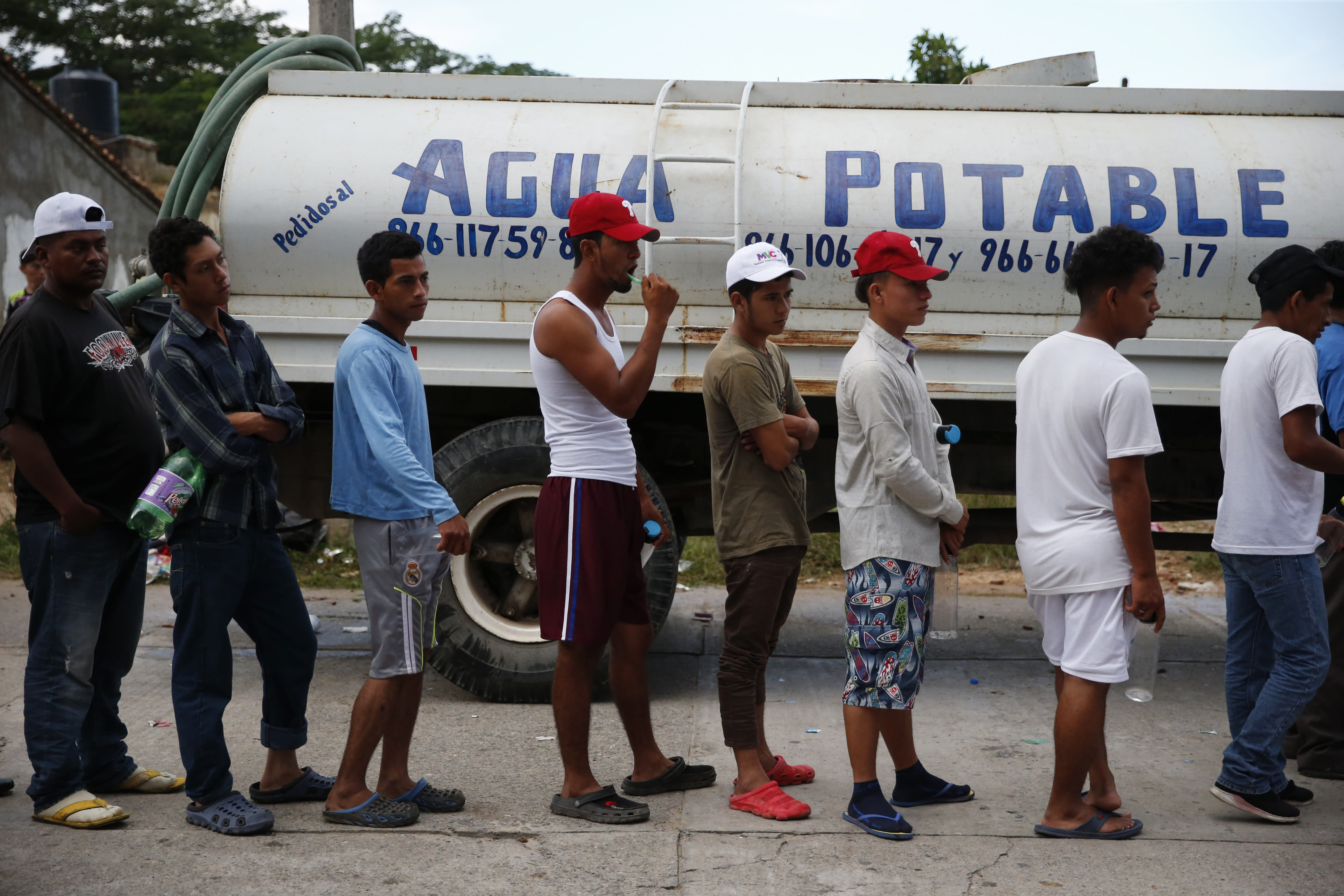 Migrants wait in line beside a water truck to brush their teeth and fill water bottles, as a caravan of Central Americans trying to reach the U.S. border halts for a rest day in San Pedro Tapanatepec, Oaxaca state, Mexico, Sunday, Oct. 28, 2018. Thousands of migrants took a break Sunday on their long journey toward the U.S. border roughly 1000 miles away, with Mexican government agencies seeming to waver between helping and hindering.(AP Photo/Rebecca Blackwell)