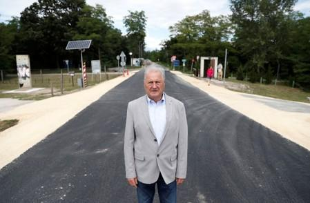Bella, former border chief poses for a photo at the Hungarian-Austrian border in Sopronkohida