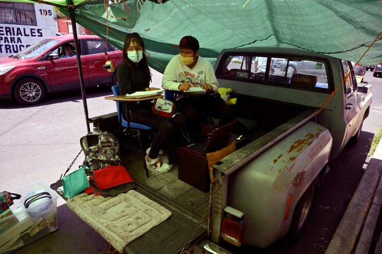 The back of a pick-up truck is one of the unusual locations for improvised classrooms at a street school in the Mexican capital