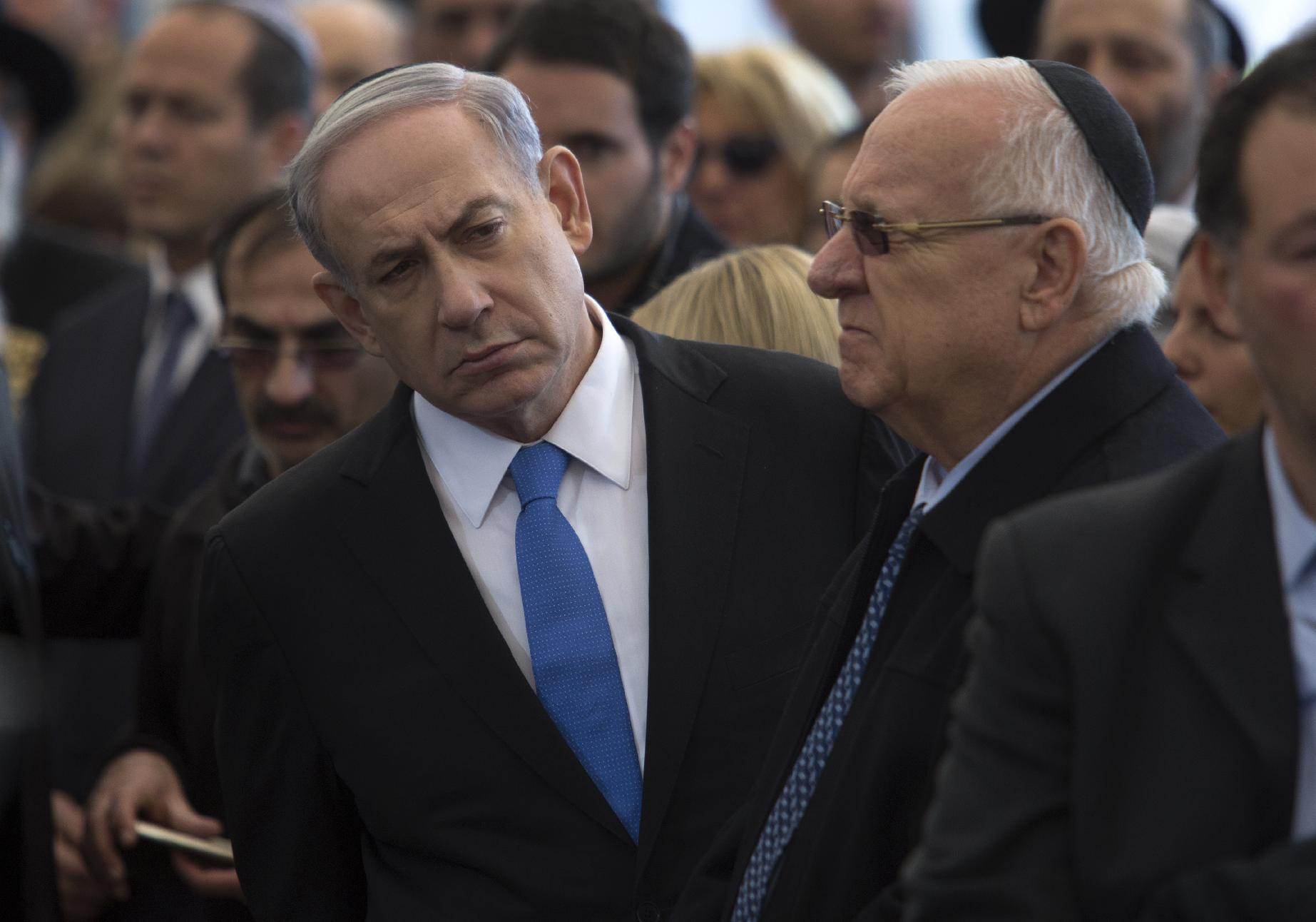 Benjamin Netanyahu leans out past Israeli president Reuven Rivlin at the funeral service in Jerusalem, on January 13, 2015, of the four Jews killed in an Islamist attack on a Kosher supermarket in Paris last week (AFP Photo/Jim Hollander)