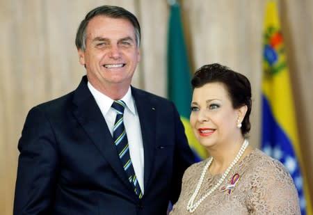 Brazil's President Jair Bolsonaro stands with Venezuela's ambassador to Brazil Maria Teresa Belandria during the credentials presentation ceremony of several new diplomats, in Brasilia