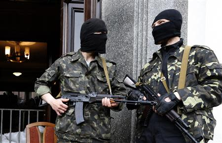 Pro-Russian armed men stand at the entrance to the regional government headquarters in Luhansk, eastern Ukraine, April 30, 2014. REUTERS/Vasily Fedosenko
