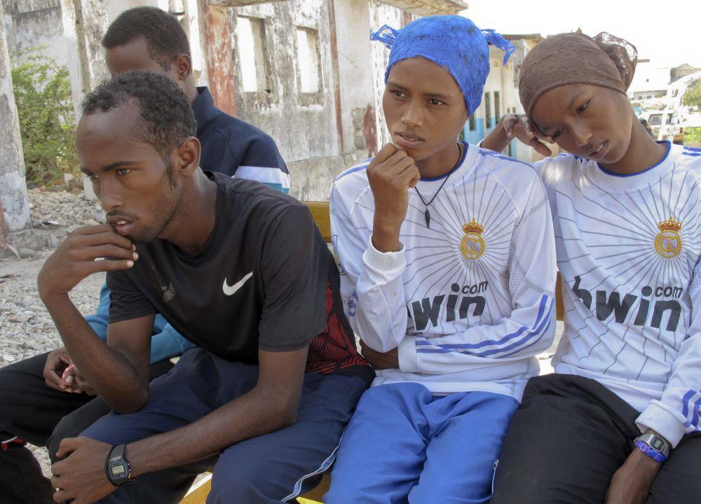 Cuatro de los cinco atletas somalíes que competirán en  los Juegos Olímpicos _de izquierda a derecha, Mohamud Ali, Mohamed Hassan Mohamed,Ayan Samow y Amal Ahmed_ observan tras un atentado con bomba que mató al presidente del comité olímpico de Somalia y al presidente de la federación de fútbol el jueves, 5 de abril de 2012, en Mogadiscio. (AP Photo/Mohamed Sheikh Nor)