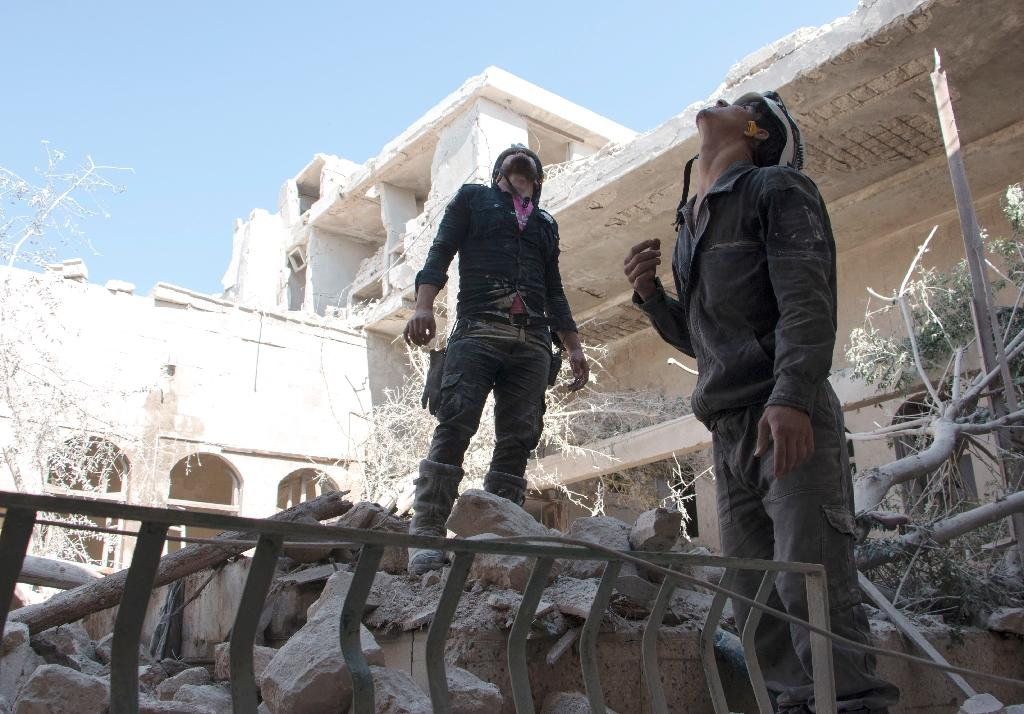 Rescue workers in the Jallum neighbourhood of the northern Syrian city of Aleppo look out for government warplanes on June 14, 2015, following a reported barrel bomb attack