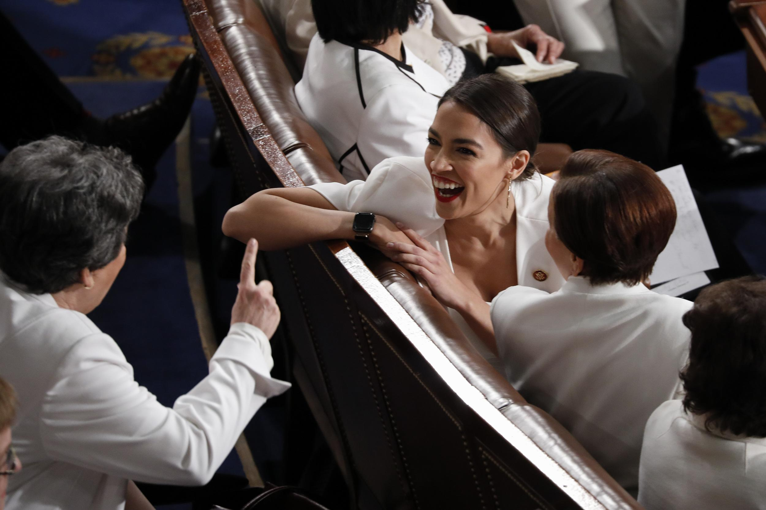 Representative Alexandria Ocasio-Cortez, a Democrat from New York, speaks with colleagues during a State of the Union address by U.S. President Donald Trump, not pictured, to a joint session of Congress at the U.S. Capitol in Washington, D.C., U.S., on Tuesday, Feb. 5, 2019. President Donald Trump cast his fight against illegal migration to the U.S. as a moral struggle, and charged in his second State of the Union address that partisan investigations threaten economic progress under his administration. Photographer: Aaron P. Bernstein/Bloomberg via Getty Images