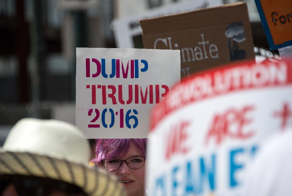 A young woman holds a sign against Republican presidential candidate Donald Trump in Philadelphia on July 24, 2016 (AFP Photo/Nicholas Kamm)