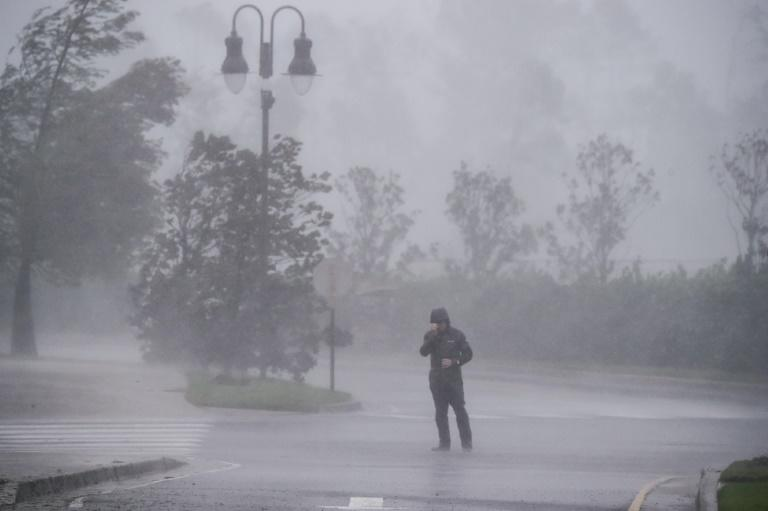 A reporter covers his face as while Hurricane Delta makes landfall in Lake Charles, Louisiana on October 9, 2020