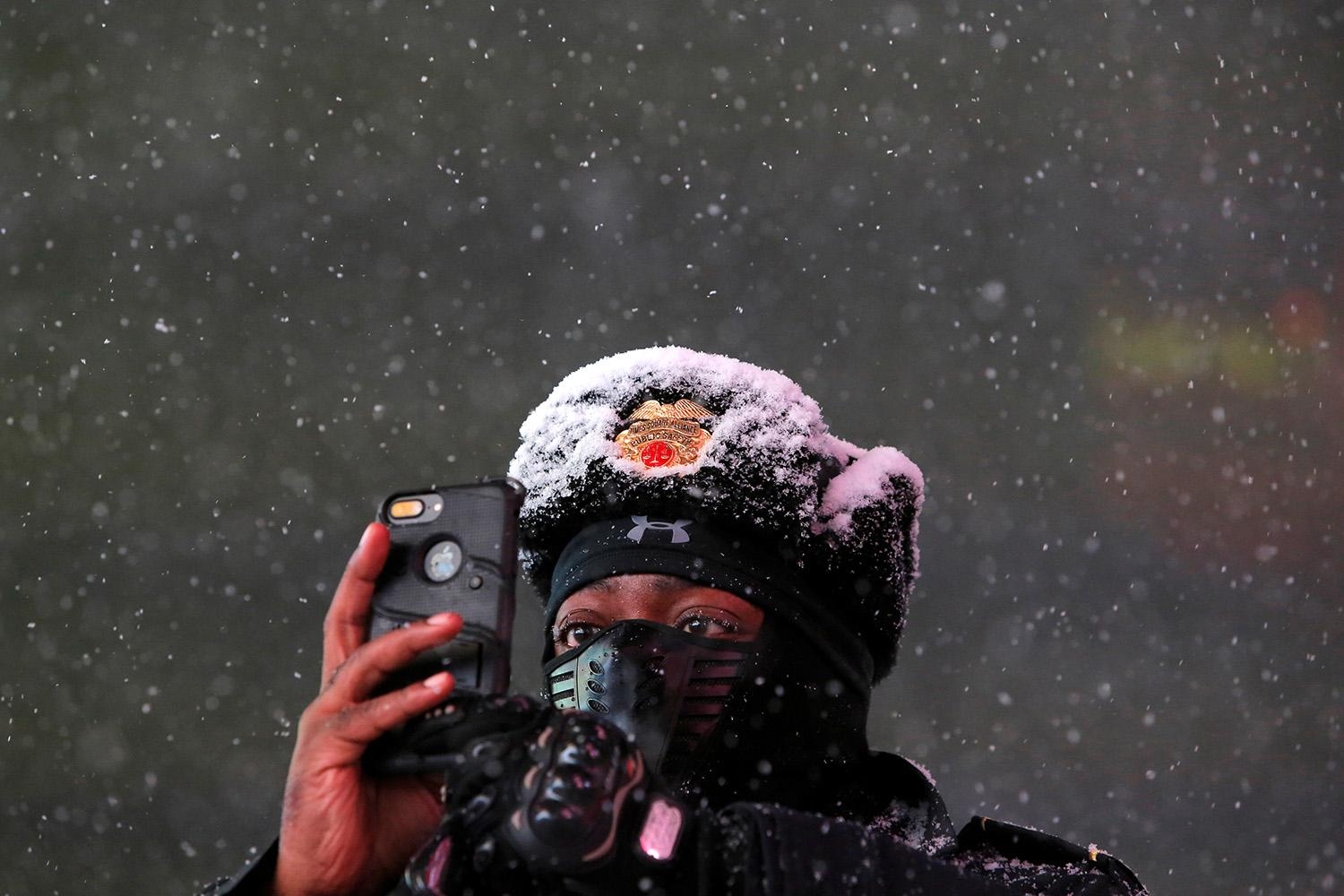 <p>Times Square Public Safety Sergeant Baldwin Davis captures falling snow with his mobile phone during a winter storm in New York, March 14, 2017. (Andrew Kelly/Reuters) </p>