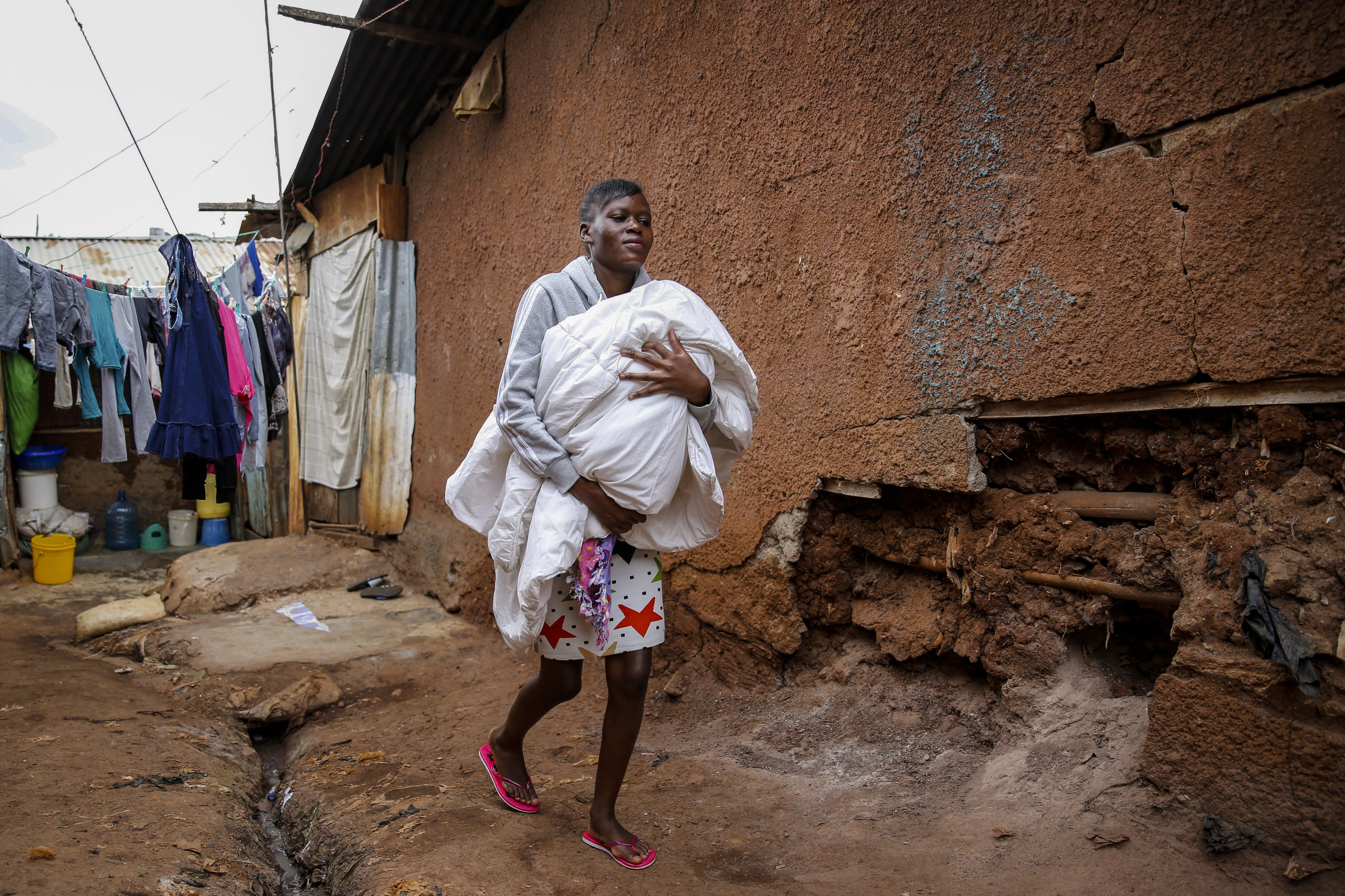 Veronica Atieno carries her daughter Shaniz Joy Juma, delivered a month earlier by a traditional birth attendant during a dusk-to-dawn curfew, in the Kibera slum of Nairobi, Kenya, Friday, July 3, 2020. Kenya already had one of the worst maternal mortality rates in the world, and though data are not yet available on the effects of the curfew aimed at curbing the spread of the coronavirus, experts believe the number of women and babies who die in childbirth has increased significantly since it was imposed mid-March. (AP Photo/Brian Inganga)