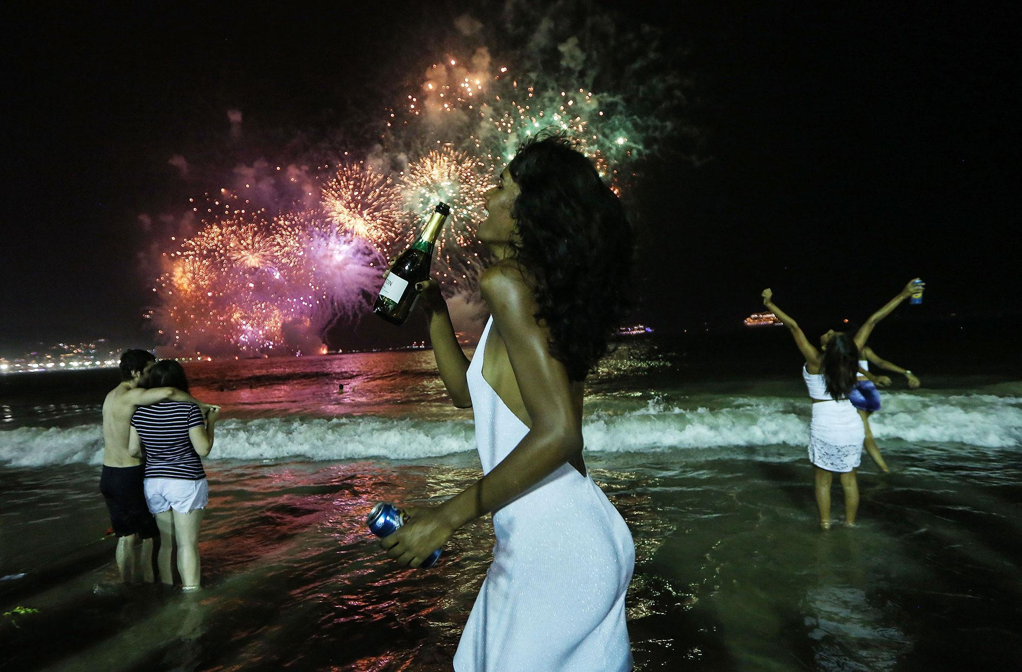 <p>JAN. 1, 2017 – Revelers celebrate during fireworks marking the start of the New Year on Copacabana beach in Rio de Janeiro, Brazil. Brazilian revelers annually mark the turn of midnight on January 1st with fireworks along the famed beach. This year's fireworks were shortened to twelve minutes due to the economic crisis facing the state and country. (Photo: Mario Tama/Getty Images) </p>