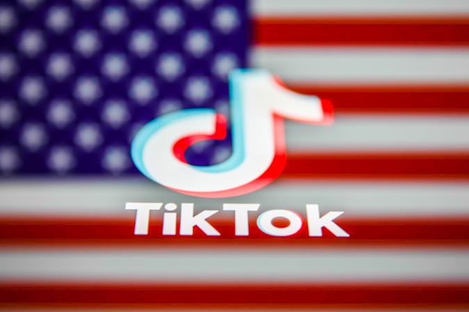 TikTok logo displayed on a phone screen and American flag in the background are seen in this multiple exposure illustration photo taken on August 3, 2020. Microsoft is interested in purchase TikTok platform in the United States. (Photo Illustration by Jakub Porzycki/NurPhoto via Getty Images)