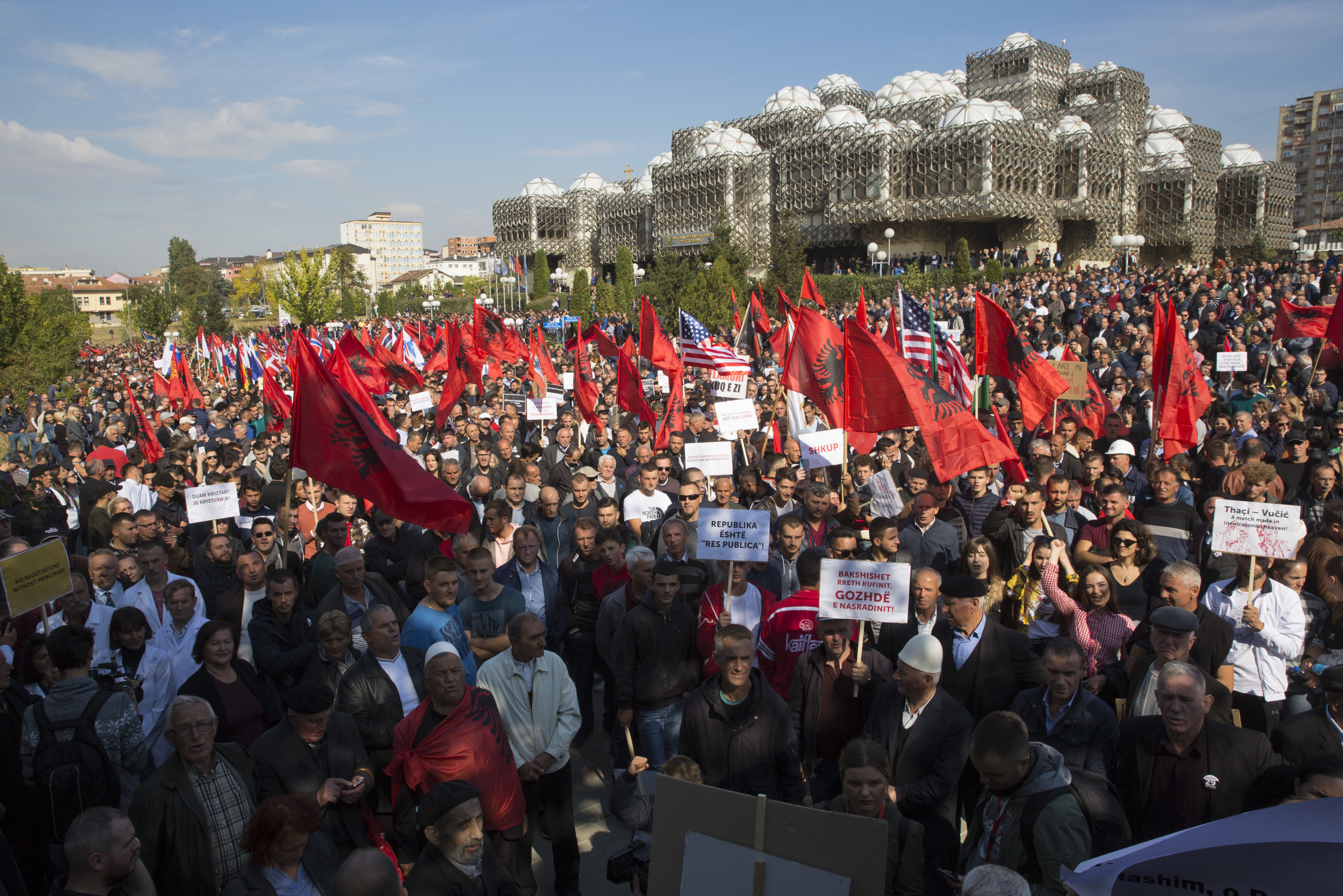 Thousands of supporters of Kosovo's opposition Self-Determination party hold banners and national Albanian flags as they march through the capital city of Pristina toward Skanderbeg Square on Saturday, Sept. 29, 2018. Thousands of people in Kosovo are protesting their president's willingness to include a possible territory swap with Serbia in the ongoing negotiations to normalize relations between the two countries.(AP Photo/Visar Kryeziu)