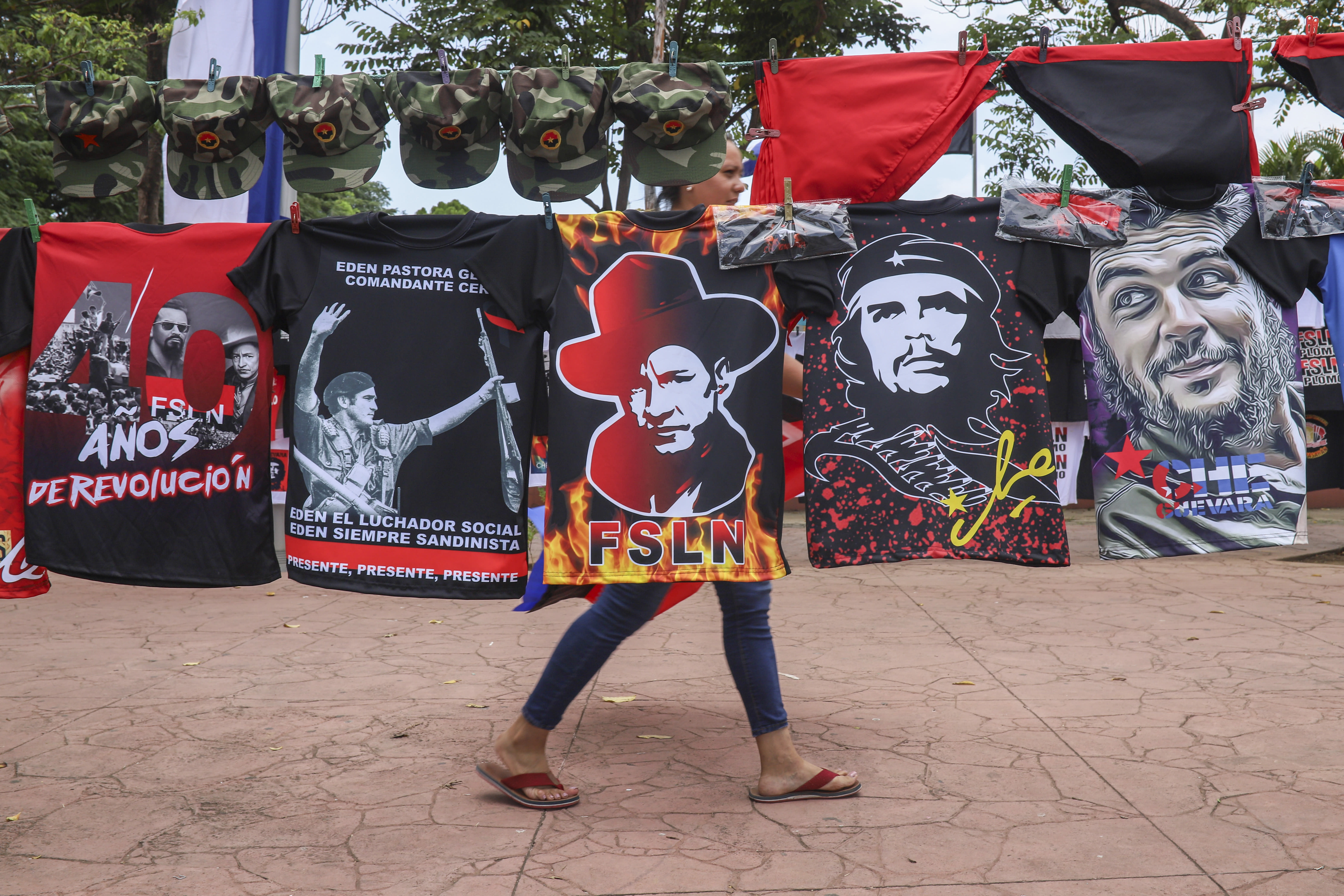 """A woman walks past T-shirts for sale promoting The Sandinista National Liberation Front ruling party on the sidelines of a new monument, called the Peace Bell, before its inauguration ceremony later in the day in Managua, Nicaragua, Friday, July 17, 2020. Nicaraguan President Daniel Ortega's government is being deterred by the new coronavirus from holding the usual mass celebration to mark the victory of the country's revolution July 19, and will instead unveil a new addition to its collection of monuments. At right are two T-shirts of Cuba's revolutionary hero Ernesto """"Che"""" Guevara. (AP Photo/Alfredo Zuniga)"""