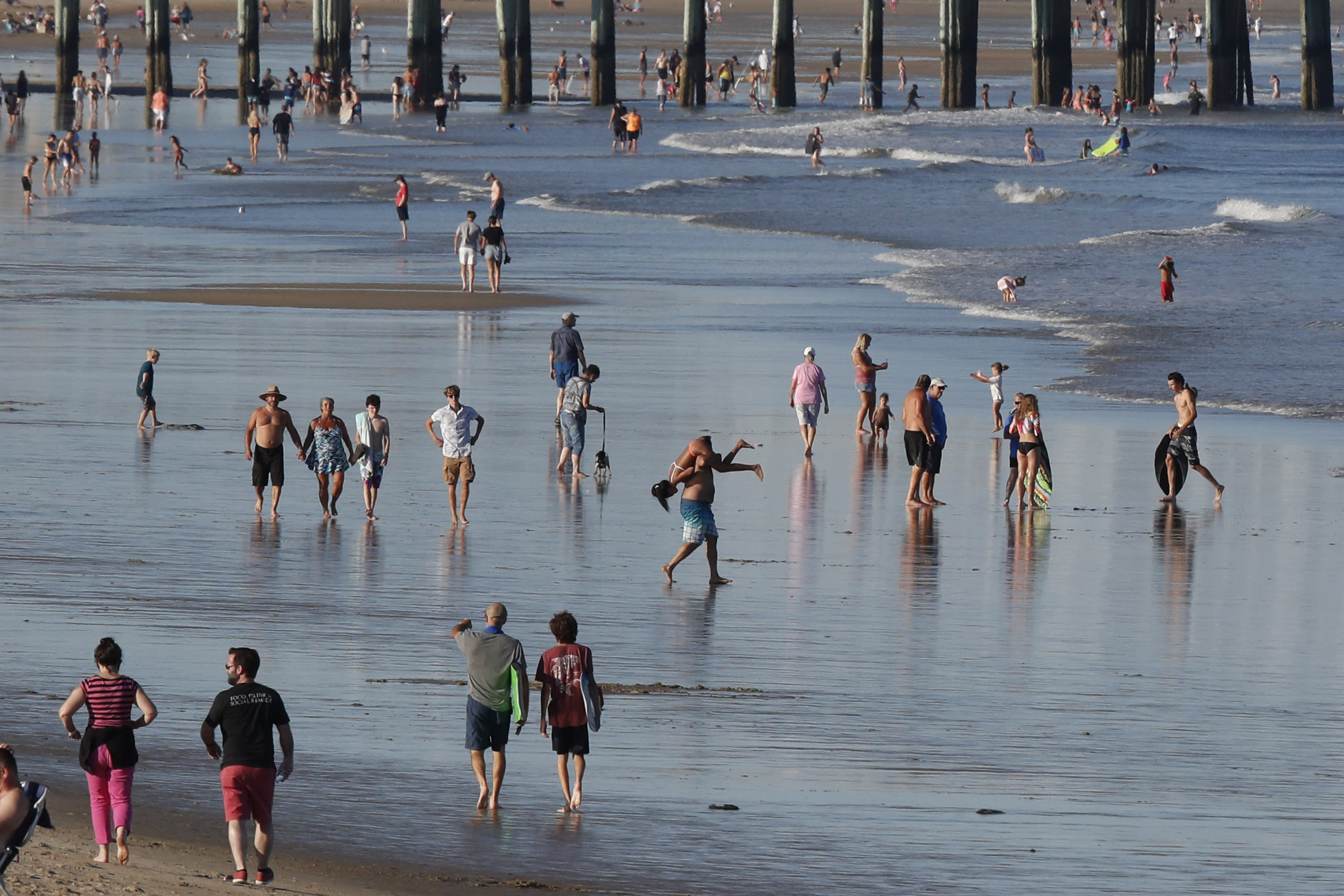 Visitors walk along the edge of the ocean, Thursday, Aug. 7, 2020, in old Orchard Beach, Maine. As the summer tourist season reaches its peak Maine's coronavirus positivity rate remains among the lowest in the nation. (AP Photo/Robert F. Bukaty)