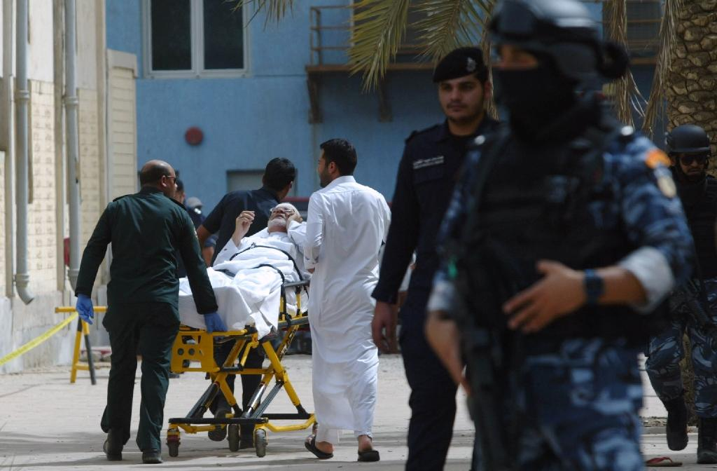 Kuwaiti emergency personnel pull a man on stretchers past security forces outside the Shiite Al-Imam al-Sadeq mosque after it was targeted by a suicide bombing during Friday prayers on June 26, 2015, in Kuwait City (AFP Photo/)