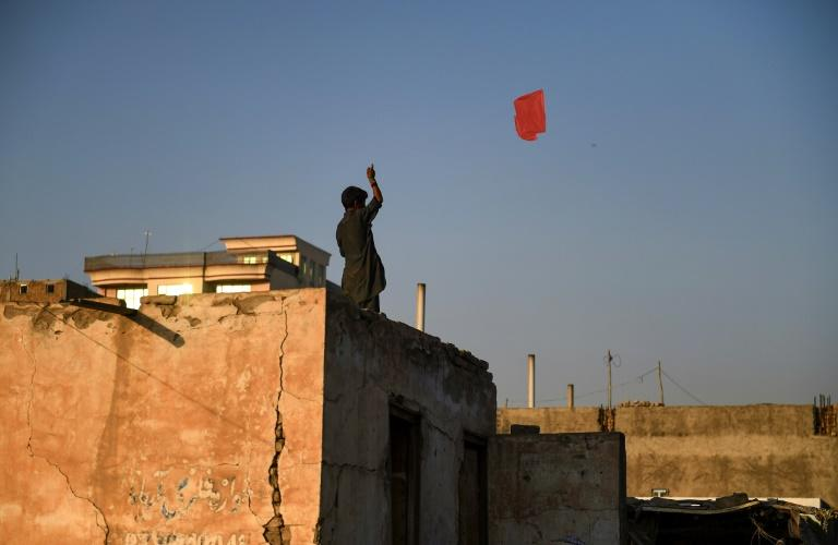 An Afghan boy flies a kite from the rooftop of a house in Mazar-i-Sharif. Young people are sceptical a deal with the Taliban will bring lasting peace (AFP Photo/FARSHAD USYAN)