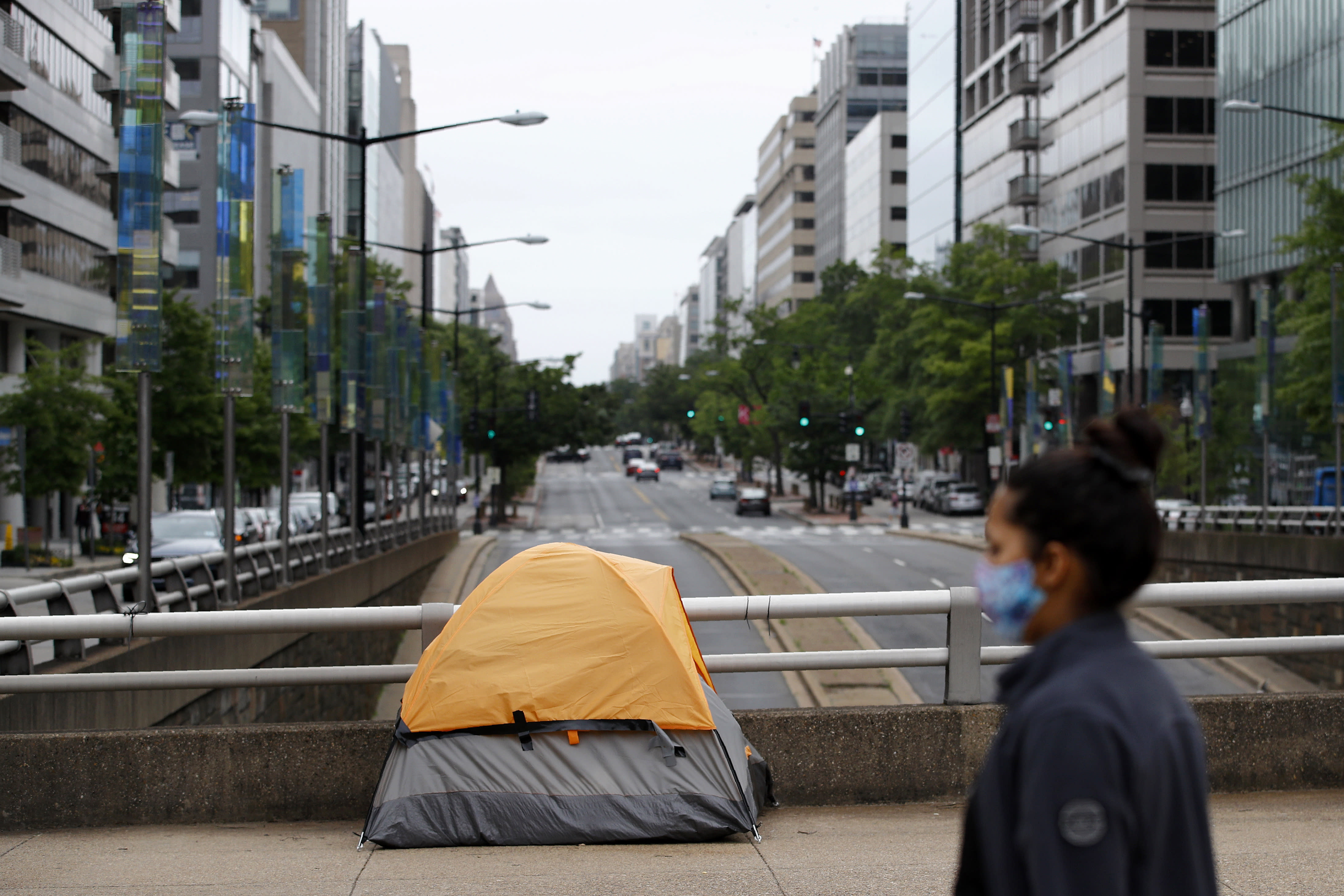 A homeless person's tent sits above a quiet K Street Northwest as a woman wearing a face mask to protect against the spread of the new coronavirus walks past, Thursday, May 21, 2020, in Washington. The District of Columbia is under a stay-home order for all residents in an effort to slow the spread of the new coronavirus. (AP Photo/Patrick Semansky)