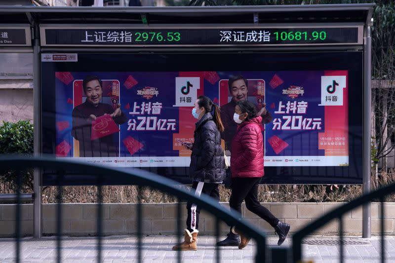 Women wearing masks walk in front of an electronic board showing the Shanghai and Shenzhen stock indexes in Shanghai