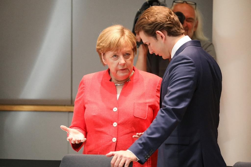 Germany's Chancellor Angela Merkel (L) speaks with Austria's Chancellor Sebastian Kurtz during the last day of the European Union leaders' summit to discuss Brexit and eurozone reforms on June 29, 2018 at the Europa building in Brussels (AFP Photo/Ludovic MARIN)