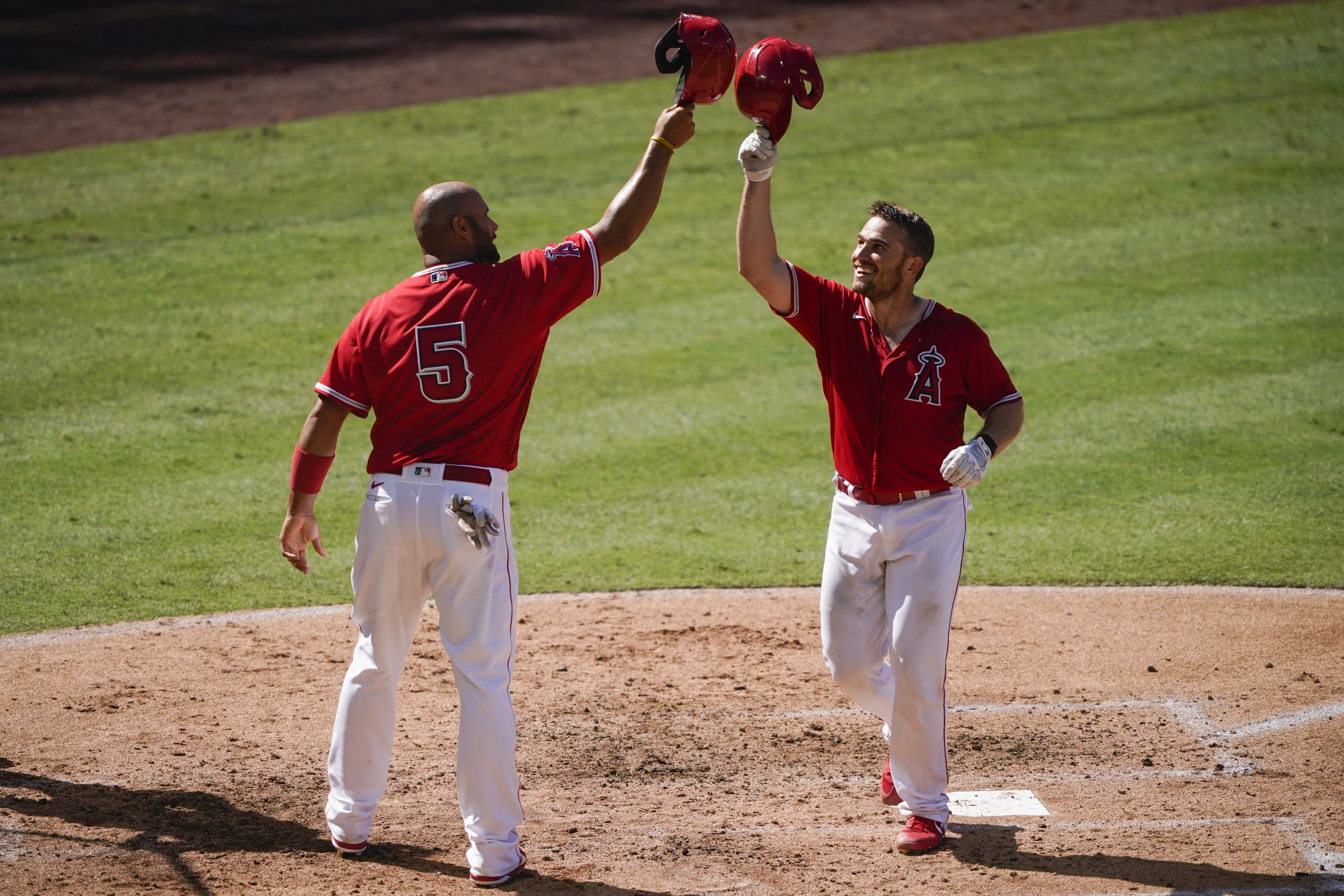 Los Angeles Angels first baseman Albert Pujols, left, hits helmets with catcher Max Stassi after Stassi hit a home run during an intrasquad game at baseball practice at Angel Stadium on Wednesday, July 8, 2020, in Anaheim, Calif. (AP Photo/Ashley Landis)