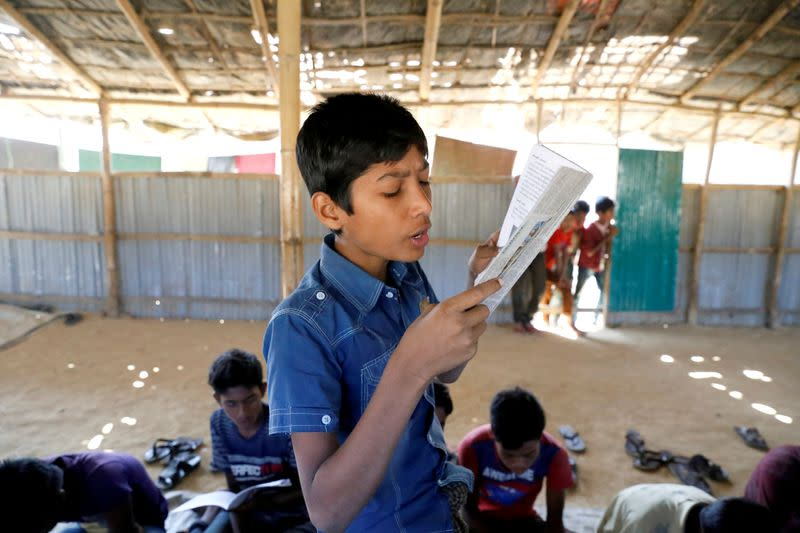 FILE PHOTO: A child reads a book in a makeshift school run by Rohingya teachers in Kutupalong refugee camp in Cox's Bazar, Bangladesh