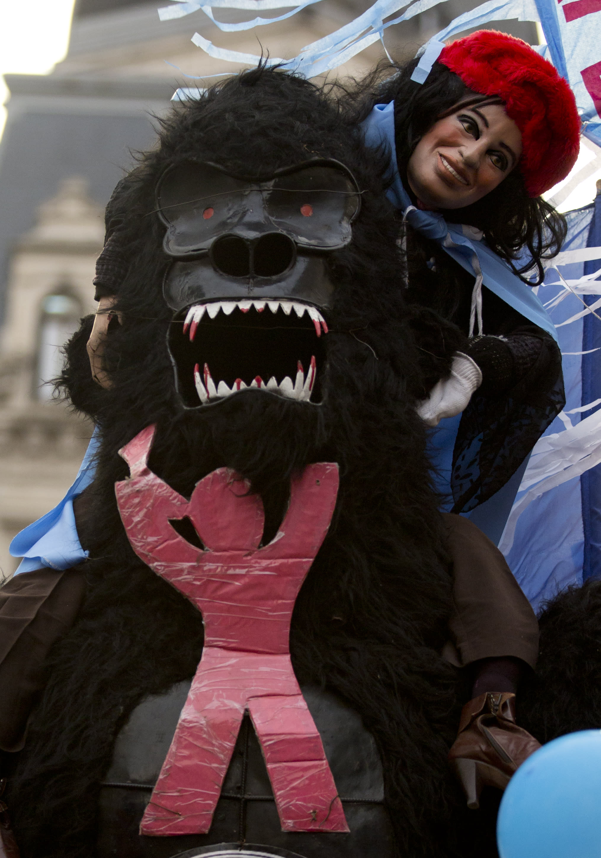 In this Oct. 17, 2013 photo, a doll of Argentina's President Cristina Fernandez sits on the shoulders of a fake gorilla with a Clarin newspaper logo attached to its chest, during a Peronist Loyalty Day rally, at the Plaza de Mayo in Buenos Aires, Argentina. The Supreme Court approved the country's four-year-old broadcast media law on Tuesday, Oct. 29, 2013, deciding that it's constitutional to force private news media monopolies to break themselves apart if they exceed government-imposed audience limits. The historic ruling is a huge victory for Fernandez and a bitter defeat for Grupo Clarin, which has been a leading voice against her administration. (AP Photo/Natacha Pisarenko)