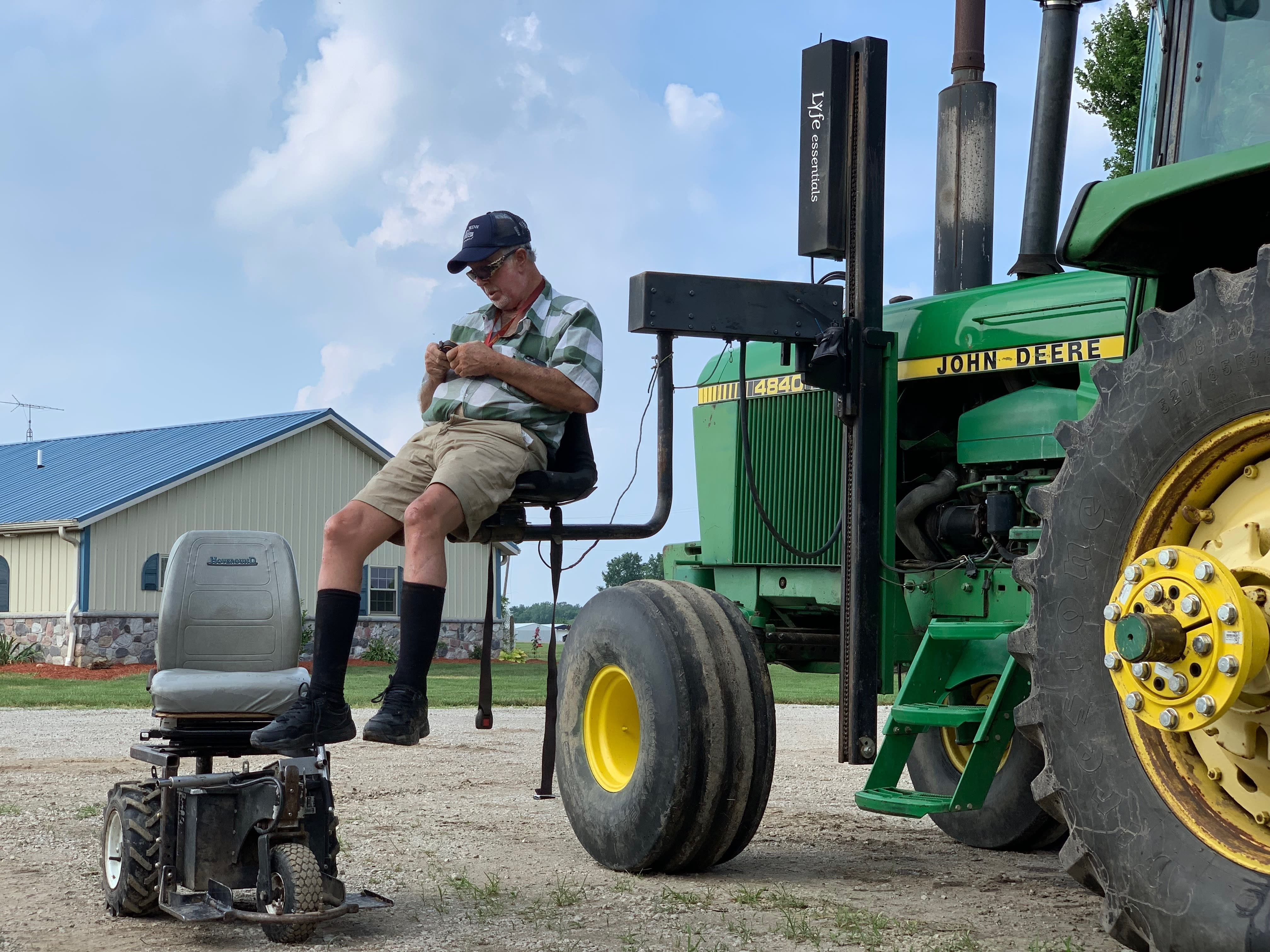 In this July 10, 2019, photo, farmer Mark Hosier, 58, uses a lift to get into a tractor on his farm in Alexandria, Ind. Hosier was injured in 2006, when a 2000-pound bale of hay fell on him while he was working. Assistive technology, help from seasonal hires and family members, and a general improvement in the health of U.S. seniors in recent decades have helped farmers remain productive and stay on the job well into their 60s, 70s and beyond. (Andrew Soregel via AP)