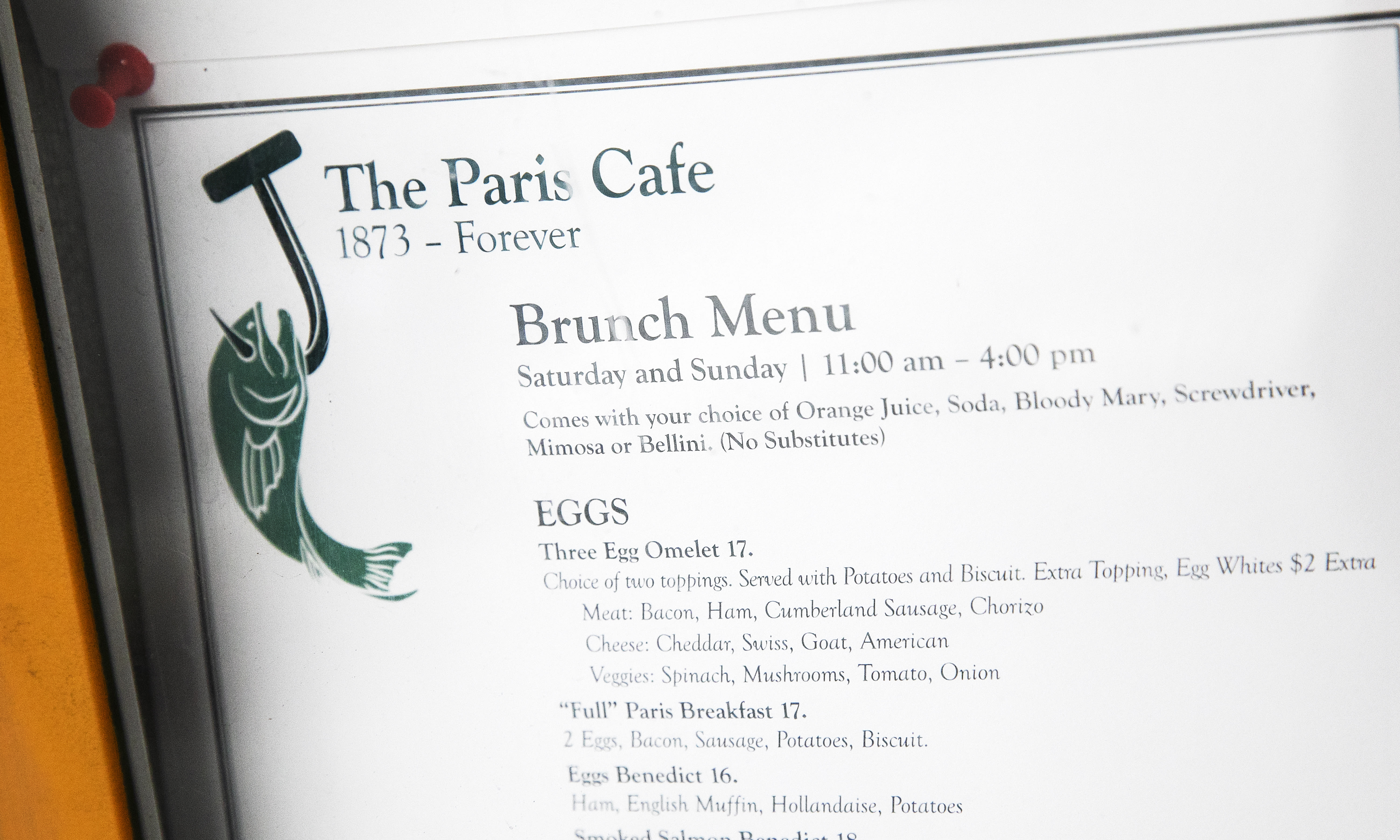 The menu for the Paris Cafe hangs in its front window, Tuesday, Aug. 4, 2020 in New York. Many iconic bars, dinners and restaurants have closed or are teetering towards closing due to the coronavirus pandemic. (AP Photo/Mark Lennihan)