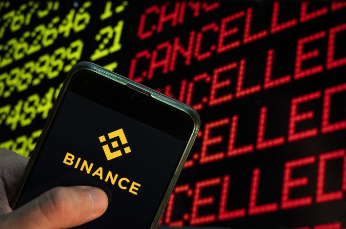 CHINA - 2021/04/24: In this photo illustration the cryptocurrency exchange trading platform Binance logo seen displayed on a smartphone with the word cancelled on a computer screen. (Photo Illustration by Budrul Chukrut/SOPA Images/LightRocket via Getty Images)