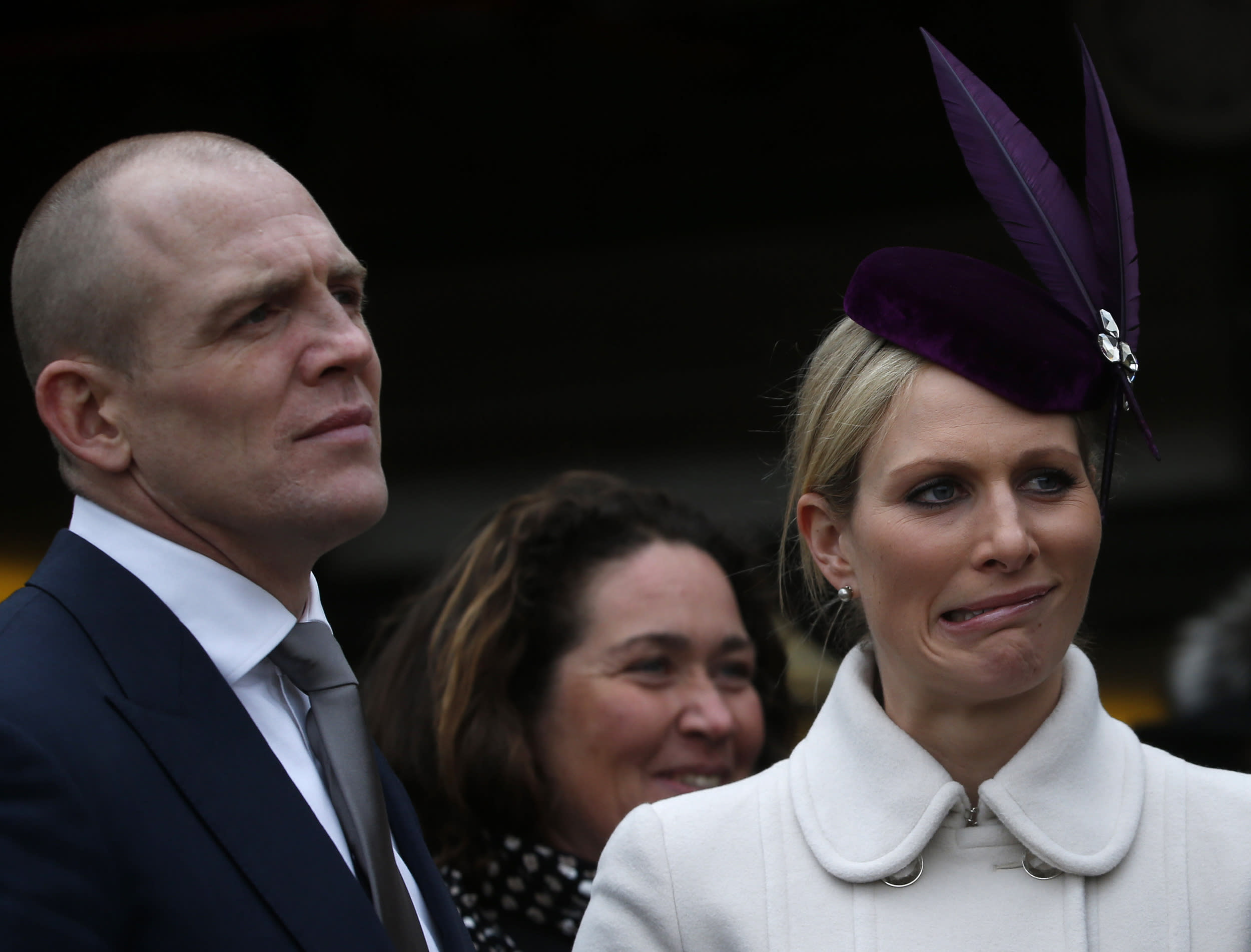 Britain's Zara Phillips (R) reacts while talking to Chanelle McCoy (unseen), the wife of jockey Tony McCoy, as her husband Mike Tindall stands by her in the unsaddling enclosure at the Cheltenham Festival horse racing meet in Gloucestershire, western England March 12, 2013. REUTERS/Eddie Keogh (BRITAIN - Tags: SPORT HORSE RACING ROYALS)