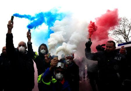 French ambulance drivers hold blue, white, red smoke bombs during a demonstration at the Place de la Concorde in Paris