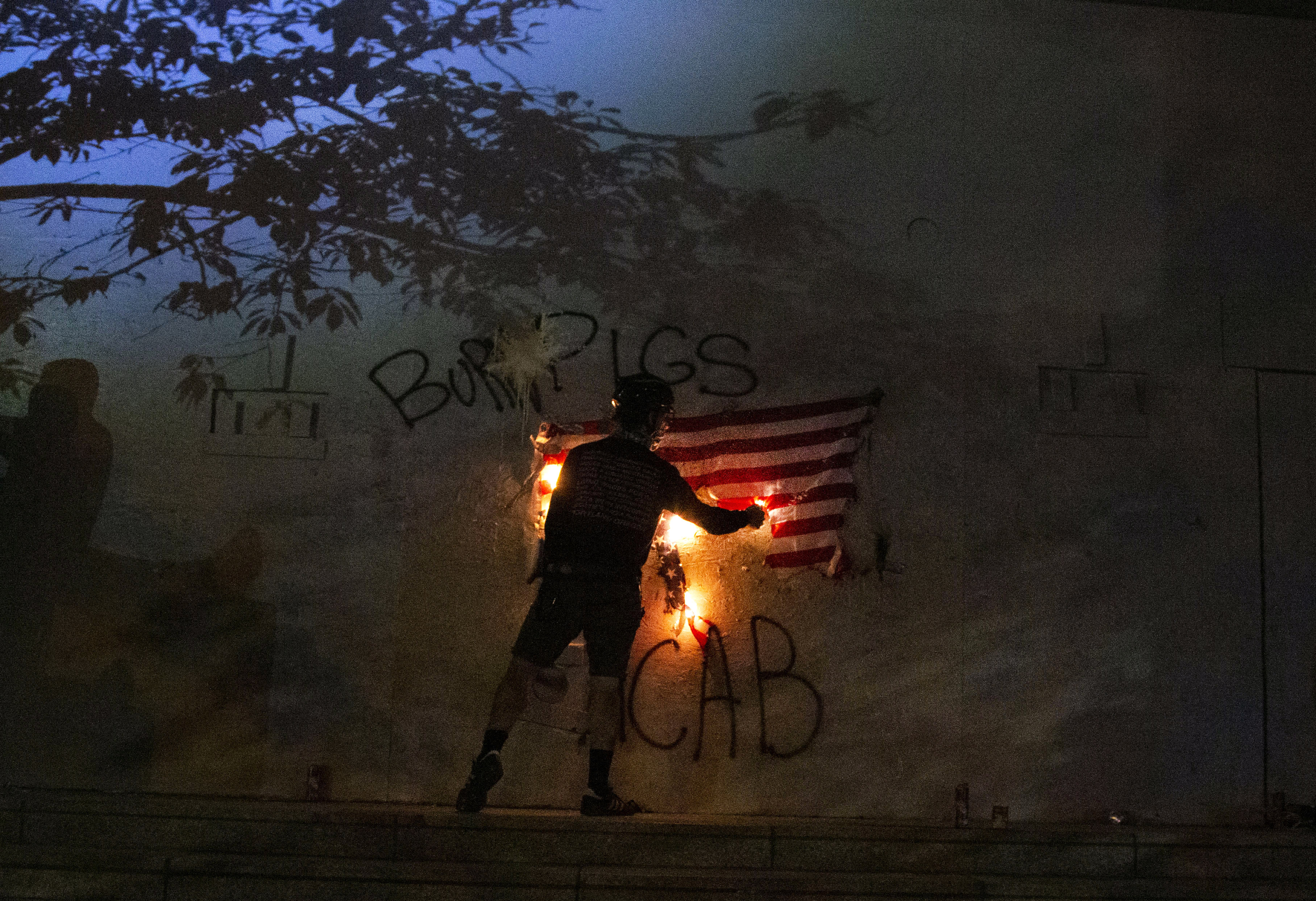 Protesters burn an American flag in downtown Portland, Ore., July 4, 2020. Portland police say more than 12 people were arrested early Sunday after throwing fireworks and mortars as they clashed with police during the latest rally decrying police brutality. (Beth Nakamura/The Oregonian via AP)