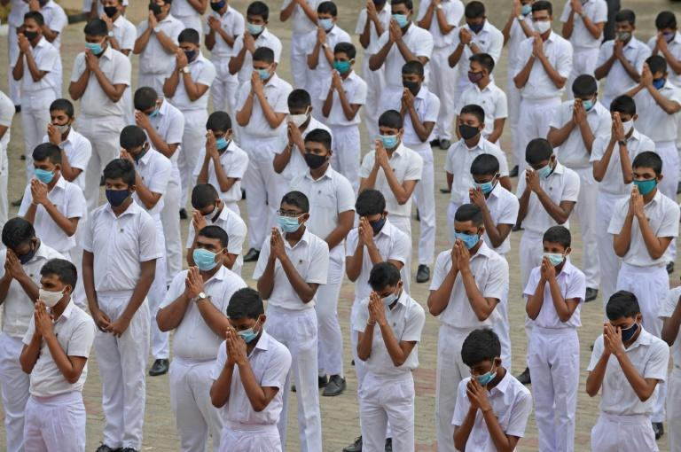 Students wearing facemasks pray after their school re-opened in Colombo on July 6. Authorities have ordered schools to close again after a surge in cases