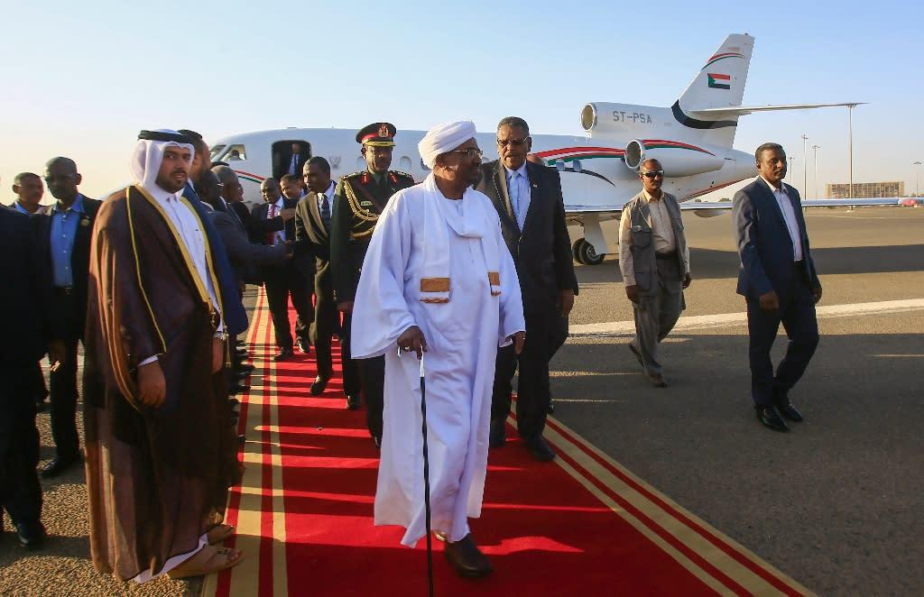 Sudan's President Omar al-Bashir (C) is received upon his return from Qatar at Khartoum international airport