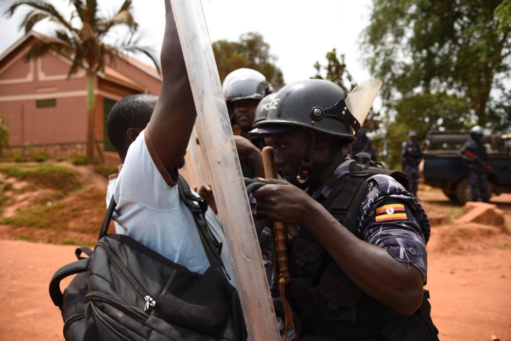 A man tries to push past police officers guarding the drive way to the home of opposition leader, Kizza Besigye, in the Kampala suburb of Kasangati on February 20, 2016 (AFP Photo/Isaac Kasamani)