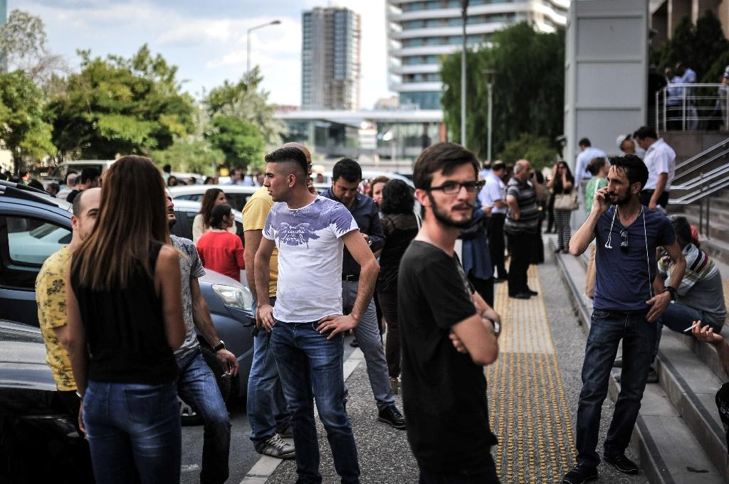 People stand in a street after they had to evacuate their buildings for security reasons following an earthquake on June 12, 2017 in Izmir (AFP Photo/Usame ARI)