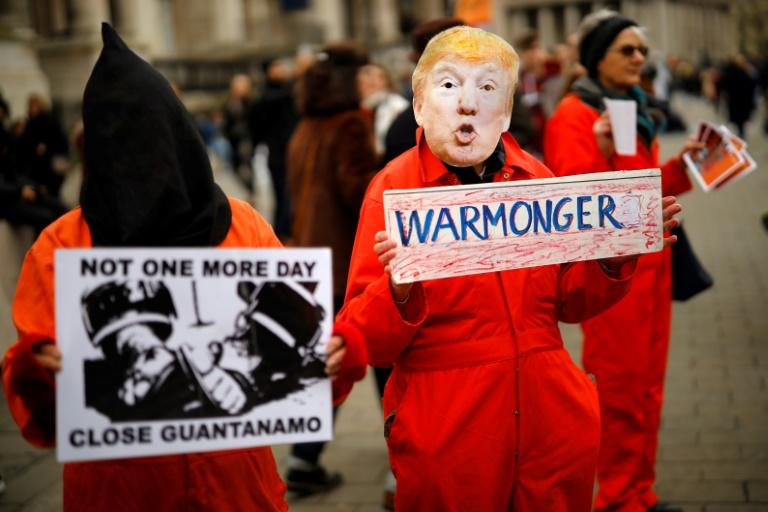 A protester holds up a placard, dressed as US President Donald Trump in Trafalgar Square during a demonstration against the threat of war on Iran, in central London on January 11, 2020