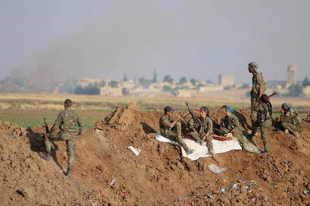 YPG fighters gather at the eastern entrance to the town of Tel Abyad