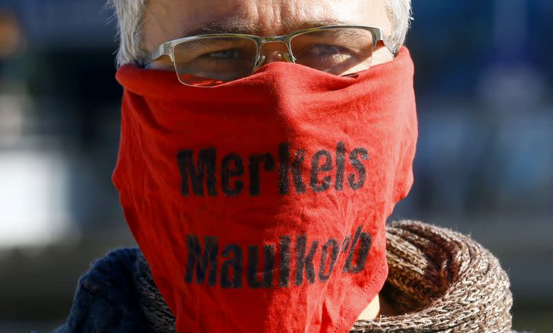 "A protester wears a mask reading ""Merkels muzzle"" during a demonstration against the government's restrictions in Konstanz"