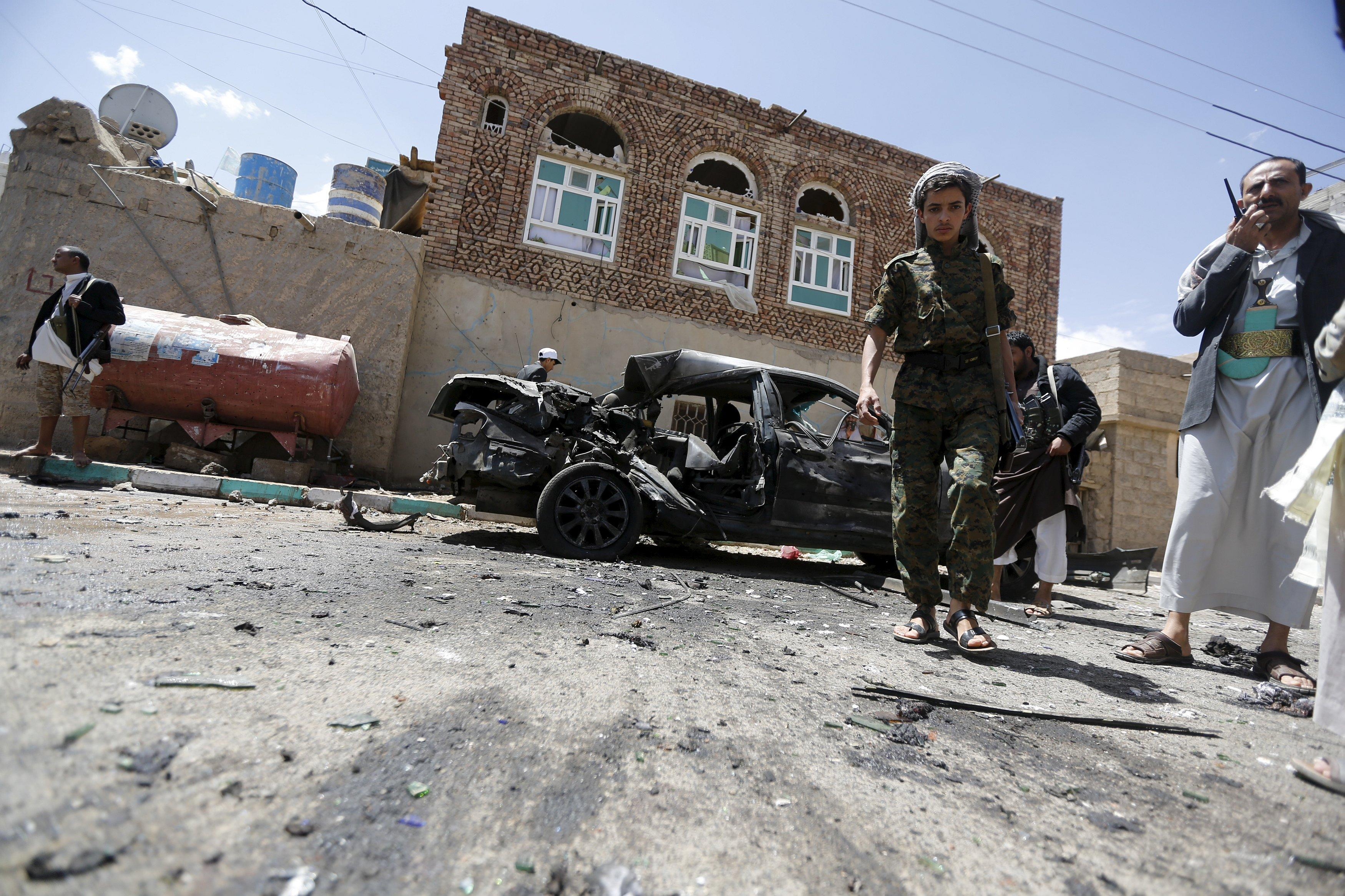 Houthi militants stand at the scene of a suicide bombing outside a mosque in Sanaa March 20, 2015. At least 87 people were killed when four suicide bombers blew themselves up in two mosques in the Yemeni capital Sanaa during Friday prayers, a medical source told Reuters. The source said at least 260 people were wounded in the blasts. Both mosques are known to be used mainly by supporters of the Shi'ite Muslim Houthi group which has seized control of the government. REUTERS/Khaled Abdullah