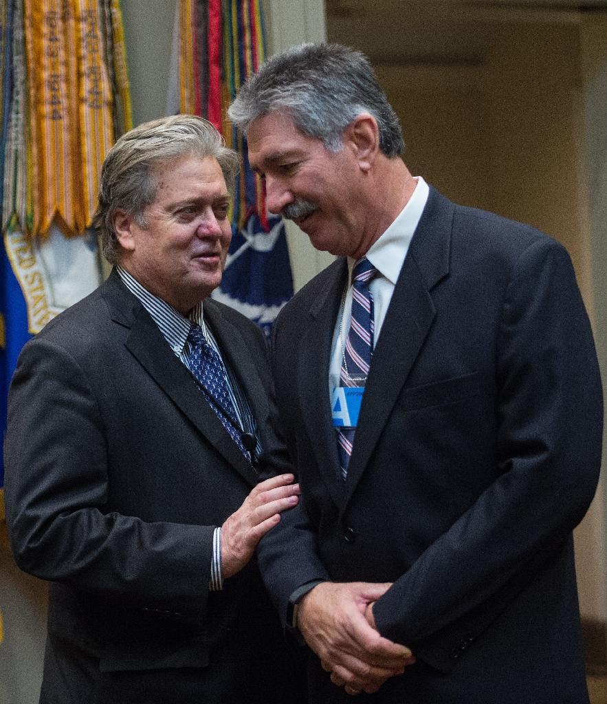 US President Donald Trump's Senior Counselor Steve Bannon (L) speaks with US Steel CEO Mario Longhi in the Roosevelt Room at the White House on January 23, 2017 (AFP Photo/NICHOLAS KAMM)