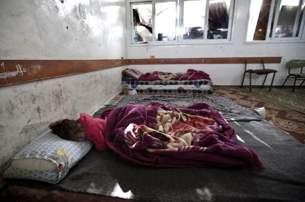 A Palestinian girl sleeps at a makeshift bedroom inside a UN-run school in Gaza City on February 25, 2015 (AFP Photo/Mahmud Hams)