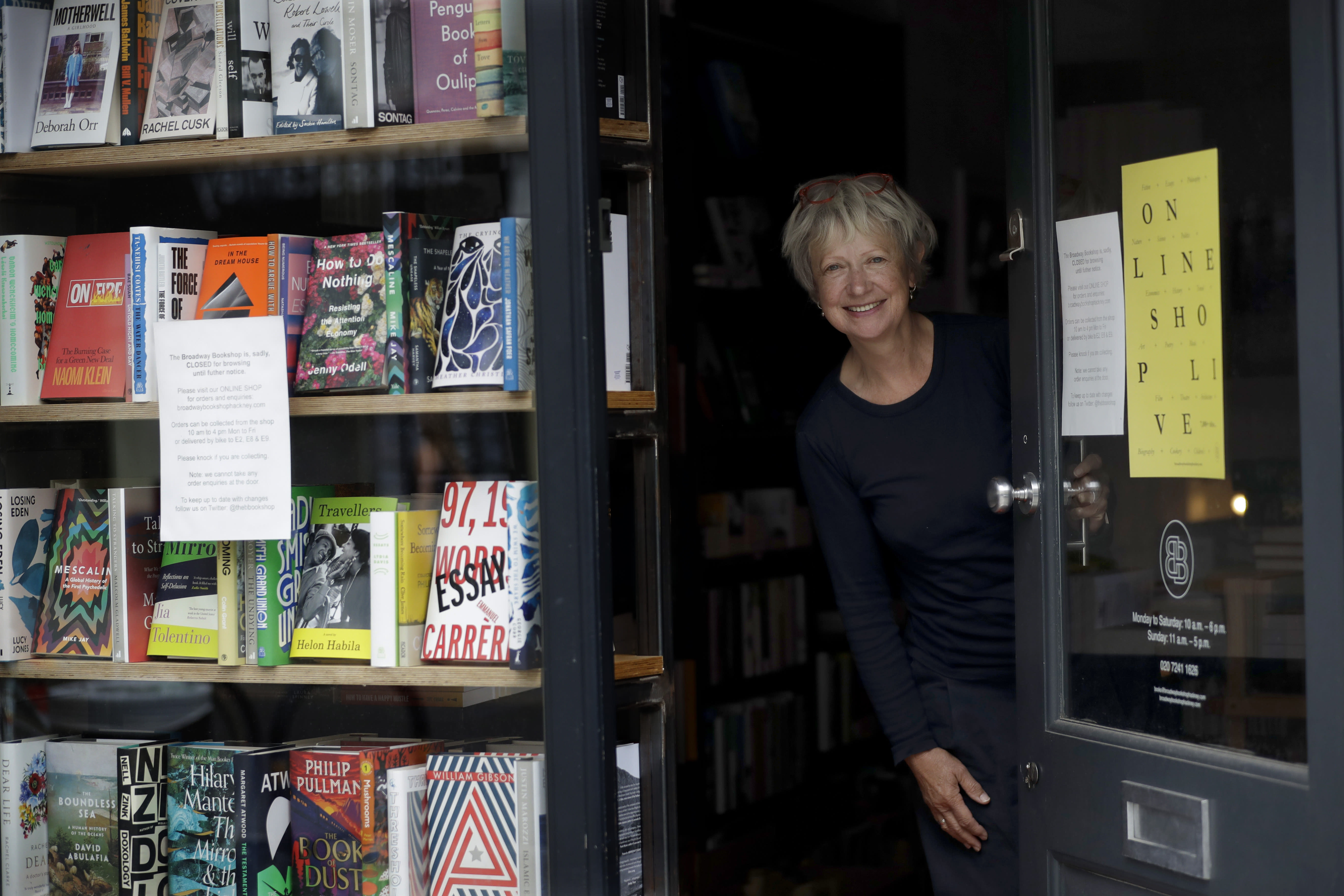 Jane Howe, owner of the Broadway Bookshop, poses for a photo in the doorway of her shop on Broadway Market in Hackney, east London on June 28, 2020. Before the coronavirus, Howe never saw the need for a website. Shoppers would pack the tidy shop on weekends, with more often waiting outside, drawn by the store's personalized service. She finally launched a website in mid-June and loyal customers have been placing orders, but sales are far below what they were before the pandemic. (AP Photo/Matt Dunham)
